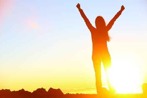 Happy celebrating winning success woman at sunset or sunrise standing elated with arms raised up-img-blog