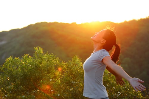 cheering woman open arms at sunrise mountain peak wellness concept-img-blog