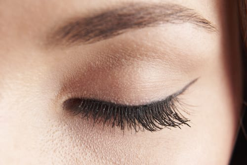 close up of womans brown eye lid with false eye lashes-img-blog