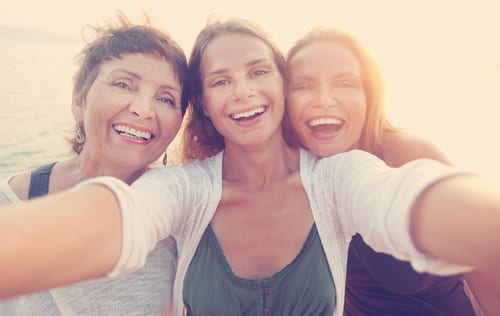 mother and two adult daughters are doing selfe on the beach-img-blog