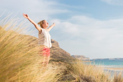woman, arms rised, enjoying sun, freedom and life an a beautiful beach-img-blog