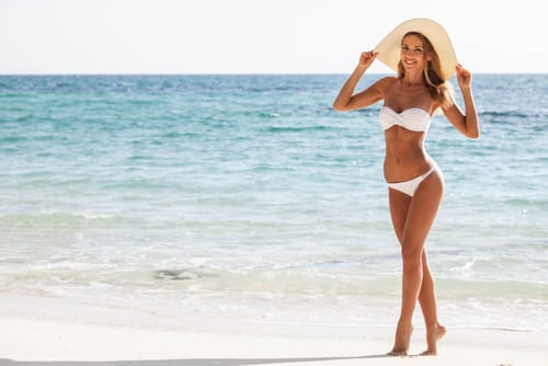 smiling woman in bikini and sunhat on sea beach-img-blog