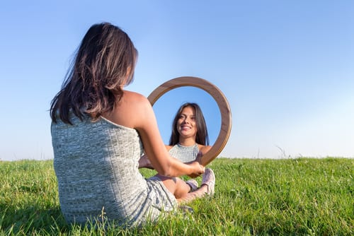 woman sitting on grass looking at her mirror image-img-blog