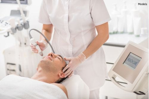 skillful-beautician-treating-a-mans-face-by-laser-img-compressor