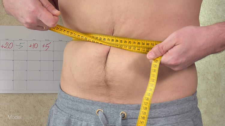 A man measures his waist to see the extra inches he's gained. Non-invasive procedures that target extra fat can be useful in reducing extra fat along the abdomen for men.