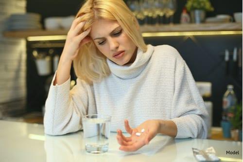 Woman preparing to take pills after surgery-img-blog