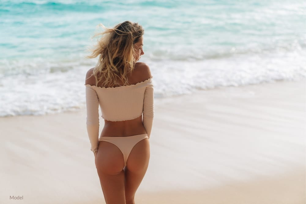 Fit woman showing off butt augmentation-like results at the beach.