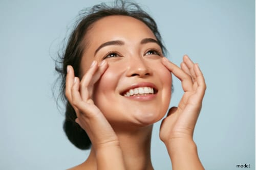 Woman admiring her clear skin as a result of healthy skin habits