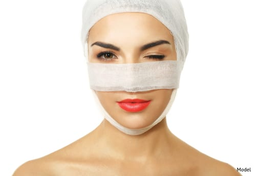Woman with face wrapped in bandages after plastic surgery.