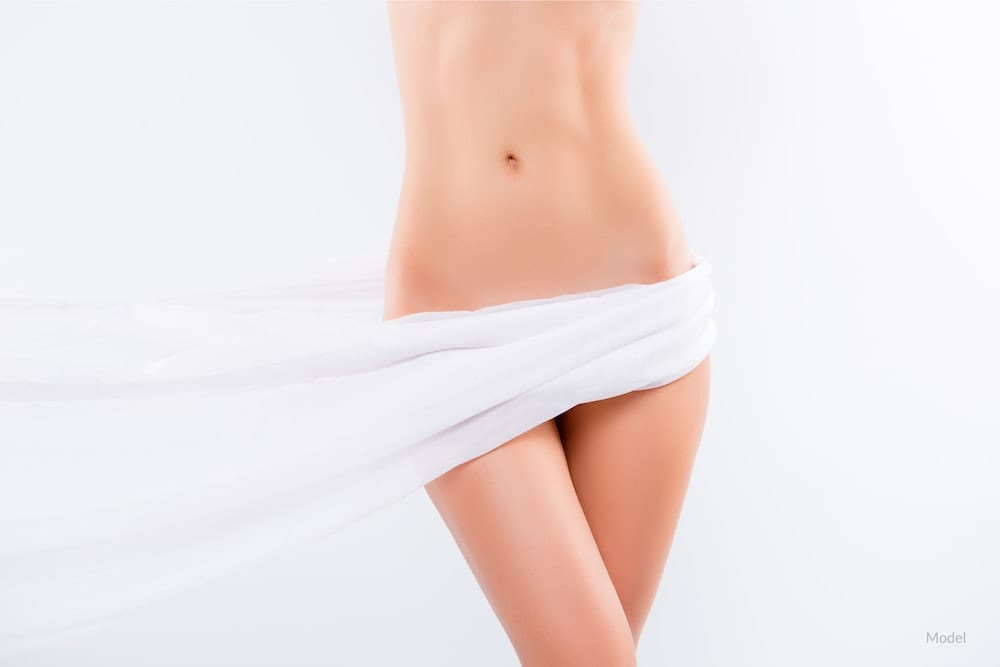 Woman with sheet over her body. Vaginal rejuvenation concept.