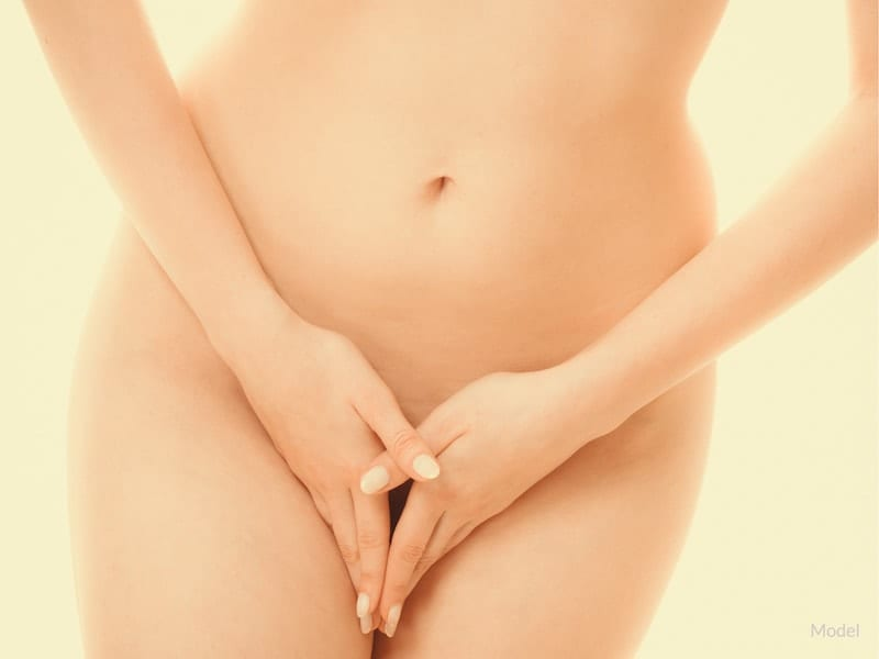A nude woman folding her fingers over her groin.