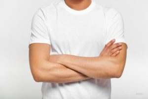 Fit man standing with his arms crossed over a white t-shirt.