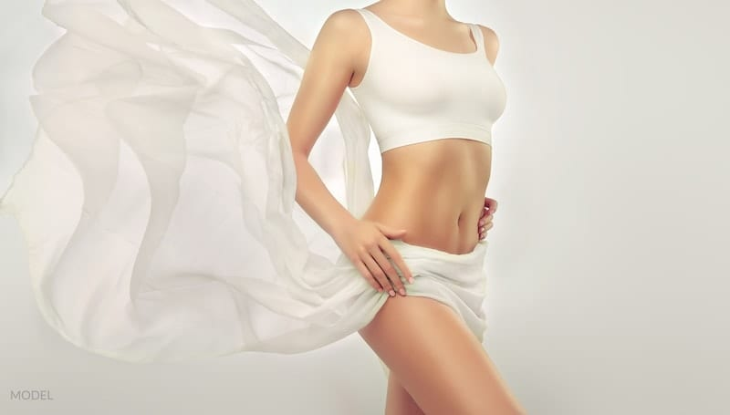 Thin, shapely woman with bare midriff and a sheet floating behind her.