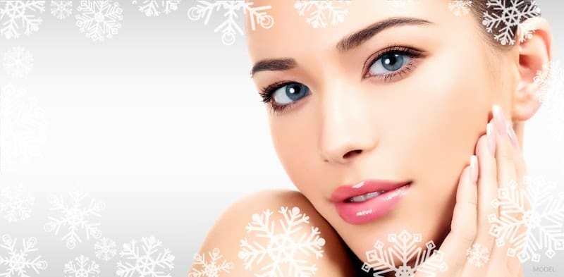 Close up of a young, beautiful woman on a gray background surrounded by snowflakes.