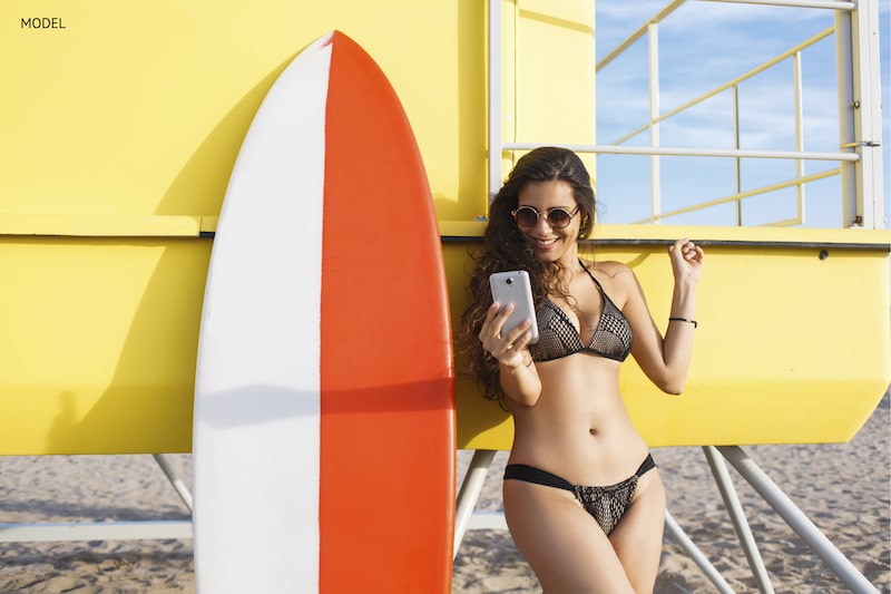 Young woman posing for a selfie next to a surfboard and lifeguard station on beach.