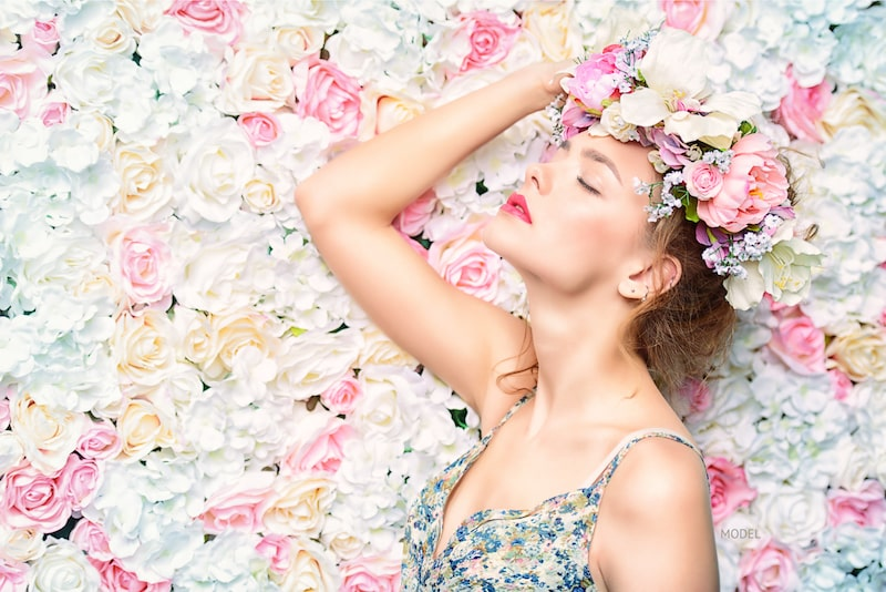 Woman standing surrounded by wall of flowers.