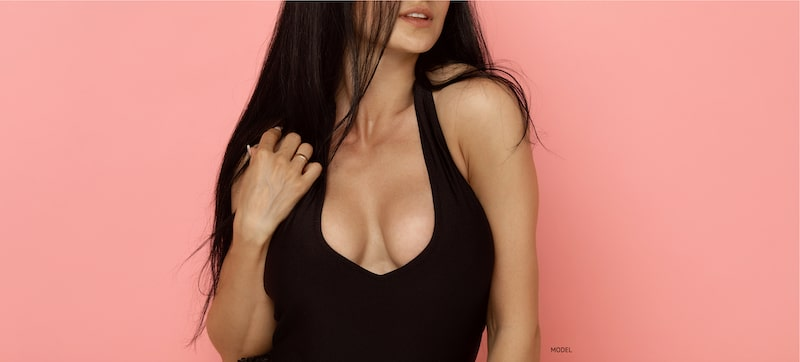 woman in a dark tank top showing off her cleavage.