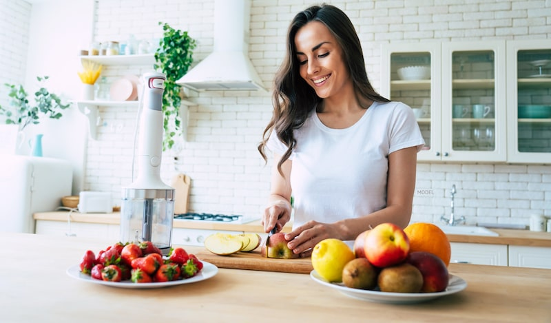 Woman cutting up fruit in kitchen