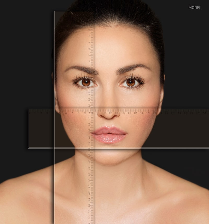 Close-up of woman's face with a ruler overlay to show facial measurements.